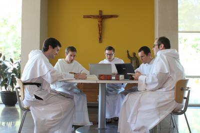 Friars studying together at a table