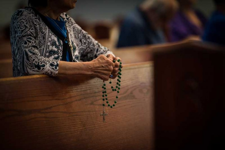 woman praying the rosary in church